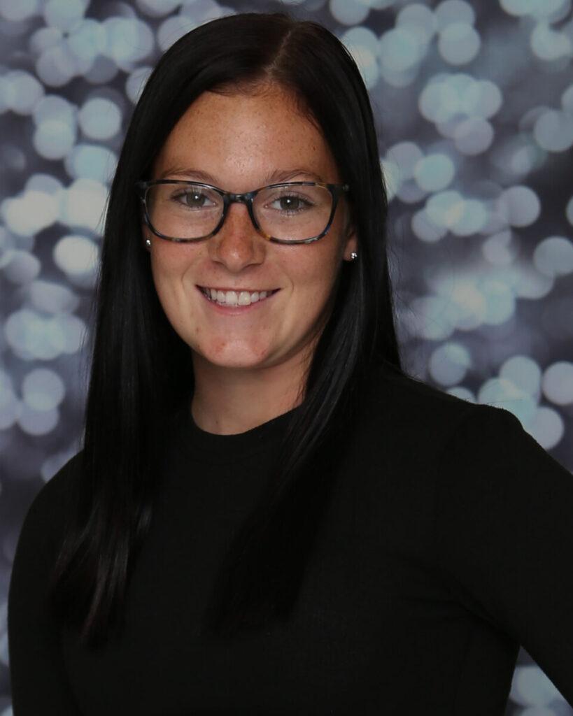 Emma Whipkey is wearing glasses and a black shirt.