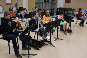 the nine band members are playing their instruments inside their classroom.